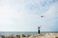 举行在天空的一个逗人喜爱的小男孩一次风筝飞行在海洋背景  图库摄影