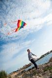 举行在天空的愉快的逗人喜爱的孩子一次风筝飞行在海背景  免版税库存图片