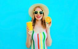 举行在她的手杯子的夏天画象愉快的微笑的妇女果汁,切片在草帽的桔子在五颜六色的蓝色 免版税库存照片