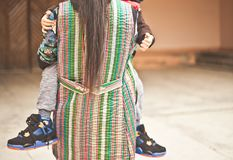 举行在她的有大运动鞋的胳膊小儿子的年轻母亲 库存照片
