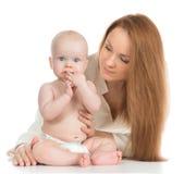 举行在她的胳膊儿童婴孩孩子女孩的年轻母亲妇女 免版税库存照片
