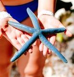 举行在妇女手上的蓝色海星,蓝色海星在白色珊瑚沙子海滩发现了在博拉凯菲律宾 海洋海岸 免版税库存照片