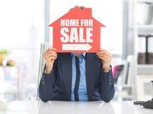 举行在家为销售标志的地产商妇女 库存照片