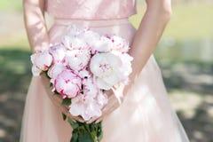 举行在手上的妇女婚姻与牡丹的花束 图库摄影
