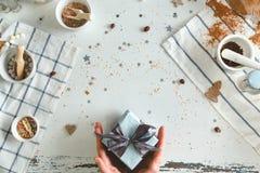 举行在手与最高荣誉的圣诞节礼物的妇女 节假日概念 顶视图 免版税库存照片