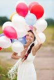 举行在手五颜六色的乳汁气球的愉快的少妇胜过 免版税图库摄影