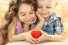 举行在手红色心脏的小男孩和女孩 免版税库存照片