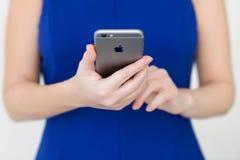 举行在手iPhone 6空间灰色的妇女 免版税库存图片