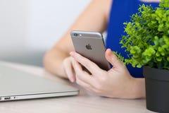 举行在手iPhone 6空间灰色的妇女 免版税库存照片