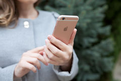 举行在手iPhone 6 S罗斯金子的妇女 免版税库存照片