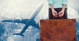 举行在日落天空的妇女手提箱和飞机飞行 库存图片