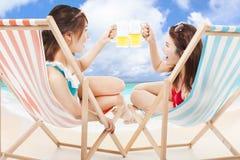 举行在海滩睡椅的两个阳光女孩啤酒欢呼 库存图片