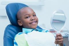 举行在牙医椅子的镜子的男孩 免版税库存照片