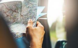 举行在男性手上和看在驾驶在背景的自动,旅游旅客远足者的航海地图的行家人全景 免版税库存照片