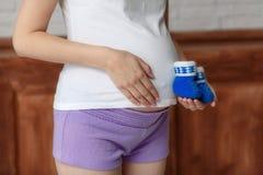 举行在腹部,特写镜头的孕妇蓝色婴儿赃物 库存照片