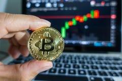 举行在膝上型计算机前面的商人金黄Bitcoin有股票的 免版税图库摄影