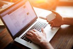 举行在膝上型计算机的男性手背面图信用卡键入的数字,当在家坐在木桌,软的焦点上时 免版税图库摄影
