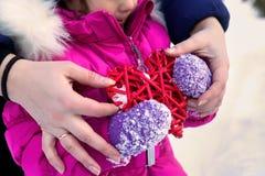 举行在他们的手心脏题材华伦泰` s天,冬天的天的小女孩在街道上的在公园 免版税库存照片