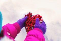 举行在他们的手心脏题材华伦泰` s天,冬天的天的小女孩在街道上的在公园 库存照片
