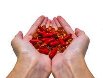 举行堆红色和黄色的胶囊在手中 免版税库存照片