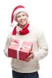 举行大红色圣诞节g的圣诞老人帽子的年轻人 免版税图库摄影