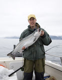 举行大银色三文鱼的愉快的渔夫 免版税库存图片