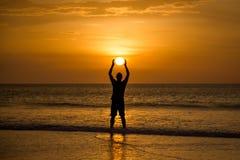 举行太阳的人 免版税库存照片