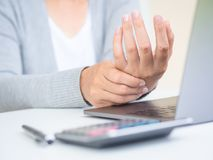 举行她的从长期使用的特写镜头妇女计算机蒂姆的手痛苦 免版税库存照片