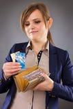 举行她的钱包和credi的一名微笑的女实业家的画象 图库摄影