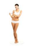 举行妊娠试验的全长愉快的妇女 免版税库存图片