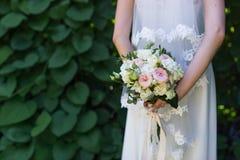 举行婚姻与桃红色和白玫瑰的新娘在她的手上花束在绿叶背景 图库摄影