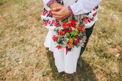 举行婚礼的妇女开花花束 免版税库存照片