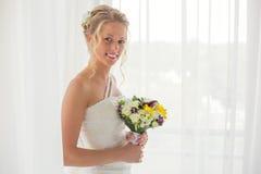 举行婚礼花束和微笑的新娘 免版税图库摄影