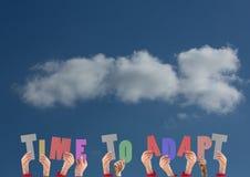 举行字时间的手适应反对天空云彩背景 库存照片