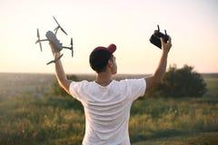 举行寄生虫方形字体直升机和遥控享用的自由,胜利,成功的人剪影 到达天空的企业概念金黄回归键所有权 库存图片