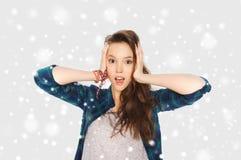 举行对在雪的头的十几岁的女孩 免版税图库摄影