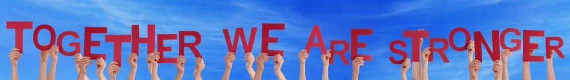 举行平直的词的手一起我们是更强的蓝天 免版税库存图片