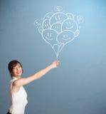 举行微笑的气球画的愉快的妇女 免版税图库摄影