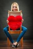 举行心形的枕头爱标志的妇女 免版税图库摄影