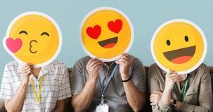 举行愉快的面孔emojis的工作者 免版税库存照片