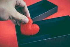 举行或投入红色的人的手心形在一件黑礼物 免版税库存照片