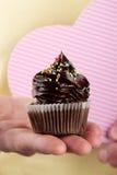 举行或提出鲜美开胃巧克力cupca的男性手 免版税图库摄影
