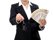 举行房子钥匙和货币的女实业家 免版税库存图片