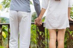 举行手后面背面图的男人和妇女站立在夏天大阳台享受热带森林美丽的景色  库存照片