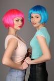 举行手和摆在的五颜六色的假发的女孩 关闭 灰色背景 免版税库存照片