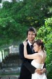 举行手和步行的新娘和新郎在庭院里 图库摄影