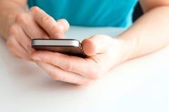 举行手机和写的男性手 免版税库存图片