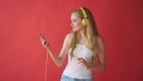 举行手机和听的音乐与耳机的年轻人相当白种人妇女在红色背景 股票录像