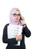 举行手机和报告的美丽的现代年轻亚裔回教女商人 免版税库存照片
