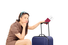 举行护照和等待的哀伤的女性游人 免版税库存照片